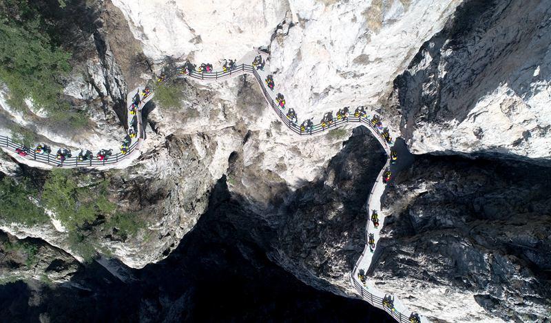 """用生命倡导生态环境:志愿者千米悬崖栈道""""飞檐走壁""""骑共享电车呼吁环保"""